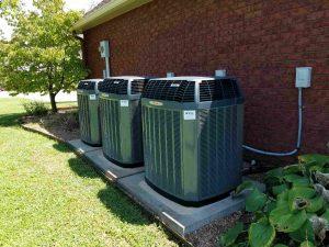 Three HVAC Units installed outside brick building.